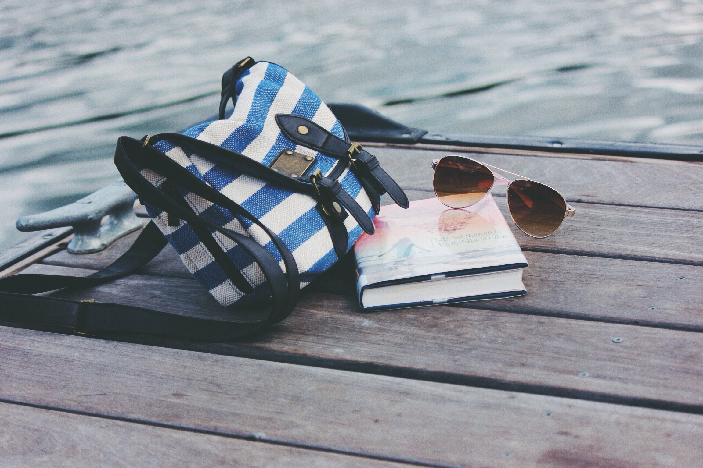 bag, book, sunglasses on a pier